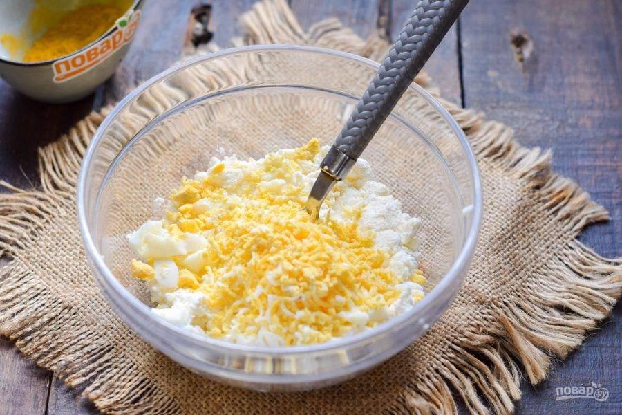 Куриное яйцо отварите вкрутую и почистите, после натрите его на мелкой терке и добавьте к творожному сыру.