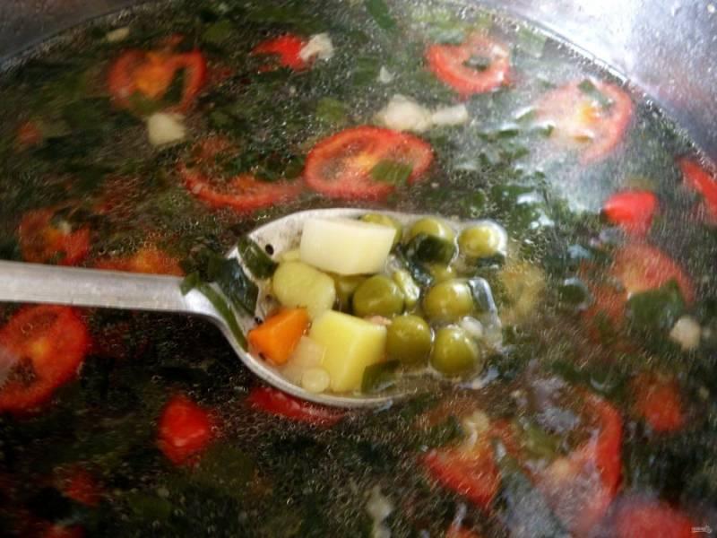 Добавьте в суп макаронные изделия и нарезанные кружочкам помидоры. Посолите и поперчите по вкусу. Варите до готовности макарон. Выложите в суп половину банки консервированного горошка, доведите до кипения. Затем добавьте в суп рубленую зелень и отключите нагрев.