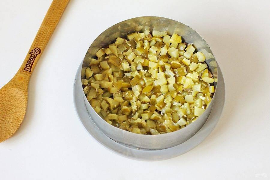 Сверху выложите нарезанные кубиками огурцы (предварительно отожмите огурцы от лишней влаги). Смажьте слой майонезом.