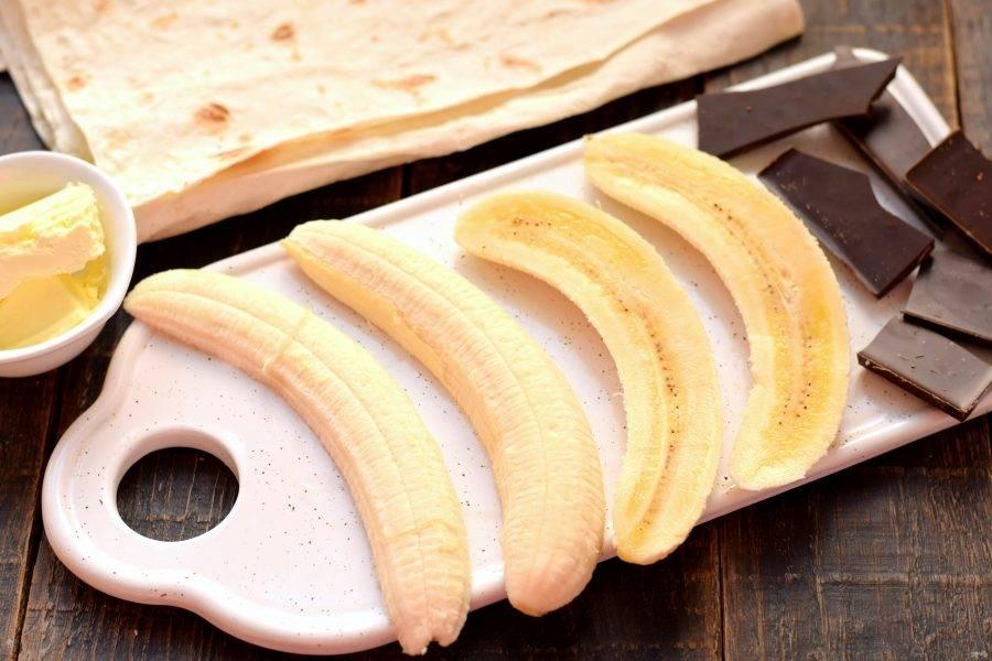 Бананы очистите от кожуры. Каждый банан разрежьте на две продольные части. Плитку шоколада поломайте на куски произвольной формы и размера.