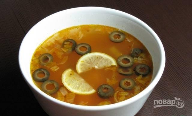 Когда картофель будет готов, добавьте в суп зажарку, оливки, огурец, перец, лавровый лист и пасту. Доведите солянку до кипения. В каждую порцию положите дольки лимона. Приятного аппетита!