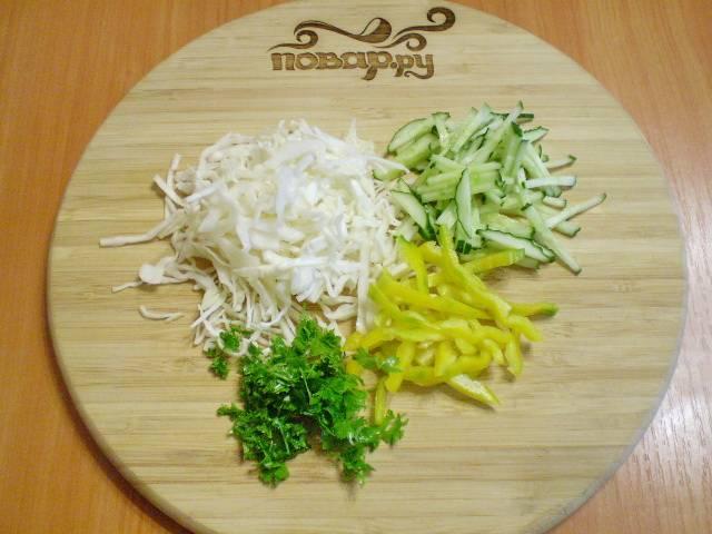 Нашинкуйте тонко капусту, порежьте огурец и болгарский перец. Порубите мелко зелень.