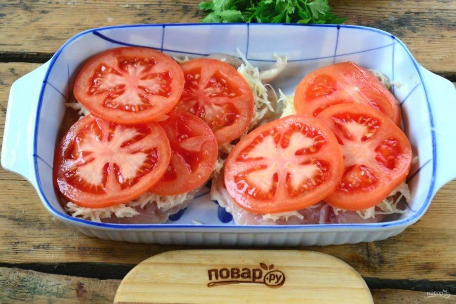 Помидор порежьте тонкими кольцами и выложите сверху на картофель.