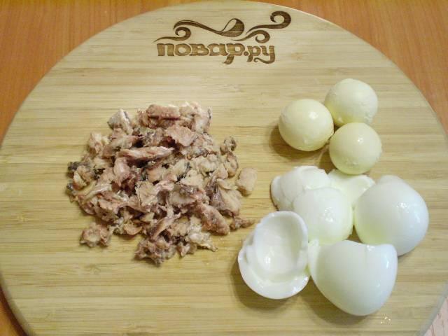 Достаньте из банки консервированные сардины. Аккуратно порежьте на небольшие кусочки. Не мните. Кусочки сардины выглядят намного аппетитнее. Остудите и очистите сваренные яйца. Отделите желтки от белка.