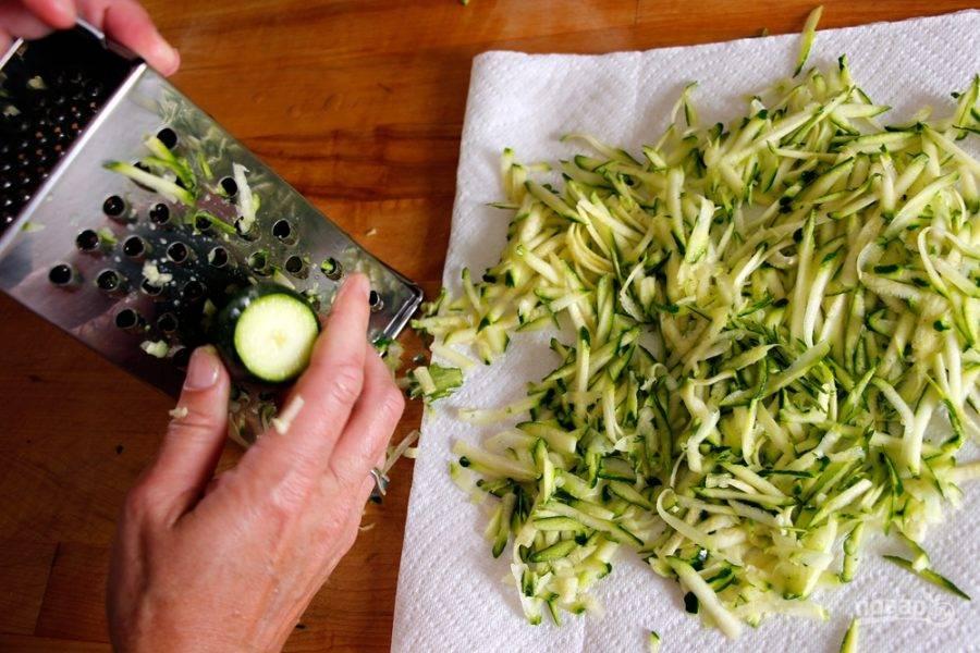 1.Вымойте кабачки, натрите их на крупной терке, затем отожмите от излишков жидкости. Нарежьте мелко зеленый лук, свежие листья мяты и кориандра.