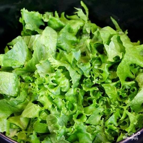 Крупно нарезаем листья салата, кладем в салатницу.