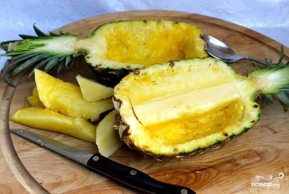 Промойте ананасы под холодной водой. Вытрите насухо. При помощи острого ножа разрежьте ананасы пополам.  Затем извлеките мякоть. Для этого держите нож под углом, надрежьте мякоть по контуру. При помощи ложки извлеките содержимое. Повторите это с двумя ананасами.