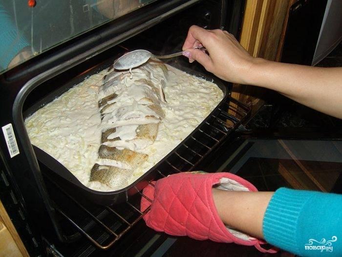 5. Соусом полейте каждый сантиметр рыбки, чтобы он был в брюшке и в каждом разрезе. Остальное вылейте на противень. В процесс подливайте соус наверх. Запекаться будет судак в духовке под сметанным соусом в домашних условиях при температуре около 190 градусов до появления сногсшибательного аромата и аппетитной корочки.
