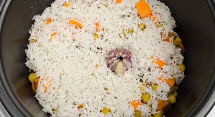 """Через 5 минут засыпаем рис, вливаем кипяченую воду, солим. В серединку кладем головку чеснока, включаем режим """"Плов"""". За несколько минут до окончания программы добавляем фисташки."""