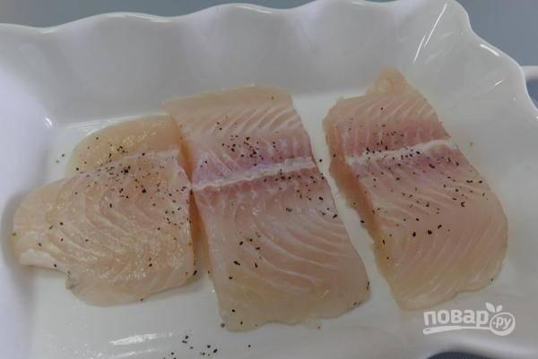 Форму для выпечки смажьте маслом. Уложите в неё рыбу. Её посолите и поперчите.