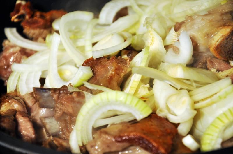 9. Когда жир полностью вытопится, достать обжаренный чеснок из сотейника и отправить туда мясо. Лук очистить, нарезать и положить в сотейник к мясу.