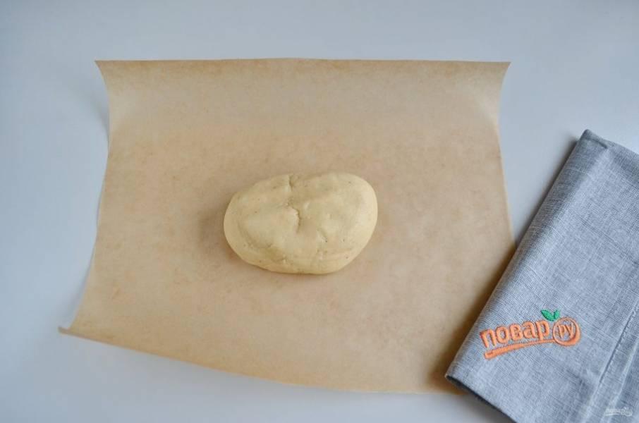 Достаньте тесто из холодильника, отрежьте небольшой кусочек, остальное уберите снова в холодильник. Положите тесто на бумагу, немного раскатайте (расплющите) по бумаге руками.