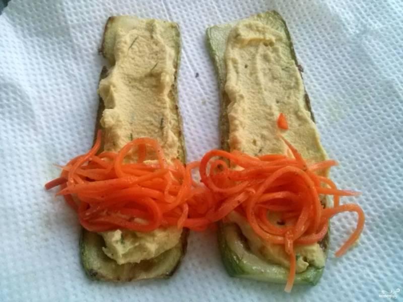 Разогрейте в сковороде масло, обжарьте ломтики кабачка до румяности. Выложите кабачок на бумажное полотенце, чтобы впиталось лишнее масло. Нанесите на ломтик яичный крем, добавьте немного корейской моркови, сверните рулетик, закрепите его зубочисткой.