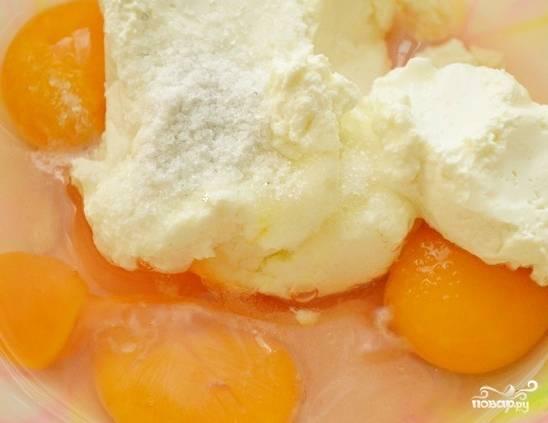 В миску разбиваем яйца, 1 желток откладываем, чтобы смазать им пирог. Добавляем творог, сахар и соль. Растираем равномерно. Кладем размягченное масло, взбиваем миксером.