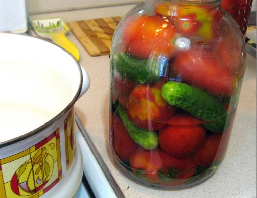 2. Каждый помидор, если боитесь, что они потом лопнут, аккуратно сразу проткните зубочисткой. Сверху положите морковку и листья, если еще остались. Кипятим воду и заливаем содержимое банок. Ждем дальше 15 минут, затем воду сливаем обратно в кастрюлю.