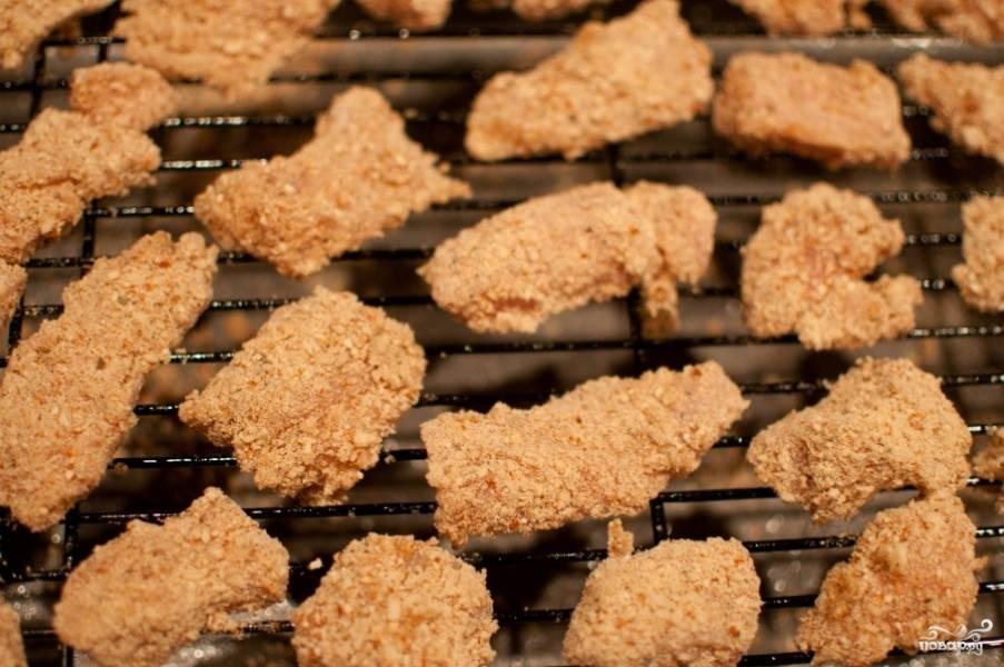 Сначала кусочек куриного филе вымочите в яичном белке, затем обваляйте в панировочных сухарях и выложите на решётку в духовку. Запекайте в разогретой на 200 градусов духовке 10 минут. Куриные наггетсы покроются хрустящей золотистой корочкой. Наслаждайтесь.
