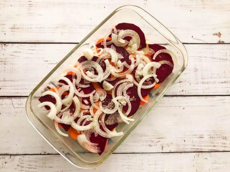 Лук очистите от шелухи, нарежьте полукольцами и выложите поверх овощей. Посолите, добавьте специи и отправьте в предварительно разогретую до 180 градусов духовку на 35-40 минут.