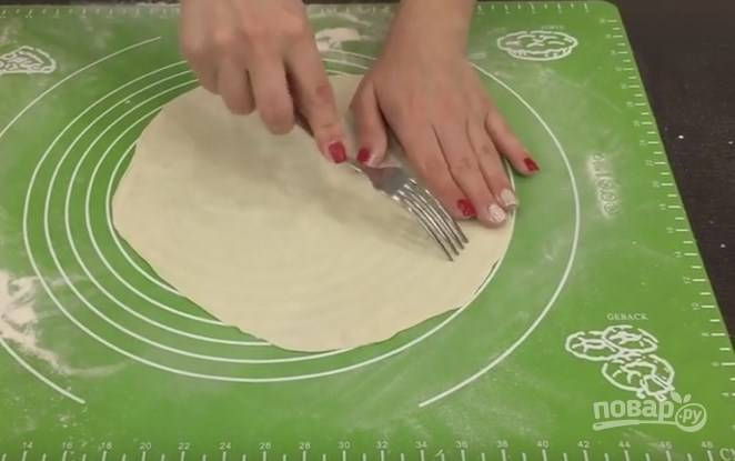 6. Стол обильно присыпьте мукой и раскатывайте колобок в обе стороны, пока он не станет совсем тонким. Затем можно взять раскатанное тесто за край и, аккуратно перебирая руками, по периметру растянуть его. Лаваш местами наколите вилкой и положите на полотенце.