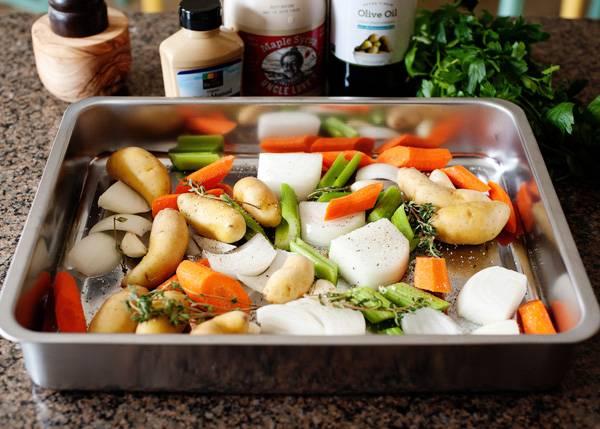 1. Блюдо совершенно несложное, так что повторить его под силу даже начинающему кулинару. Для начала очистите овощи, нарежьте крупными кусочками и выложите в жаропрочную форму. Молодой картофель можно запекать в кожуре. Использовать в рецепт приготовления курицы с овощами под соусом можно также баклажаны, сладкий перец или брокколи, например. Добавьте сверху щепотку соли и присыпьте травами.
