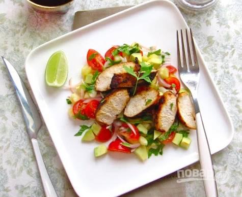 На тарелку высыпаем помидоры, кубики авокадо, сбрызгиваем все соком лимона, выкладываем сверху порезанную грудку, присыпаем все зеленью.