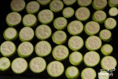 Нарежьте кабачок кружочками, которые затем выложите на смазанный жиром противень и поставьте в разогретую до 200 градусов духовку на полчаса.