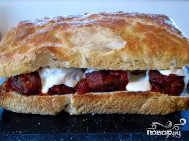 6.  Как только сыр расплавится и начнет бурлить, удалить сэндвич из духовки, накрыть сверху половинкой хлеба, острым ножом нарезать на равные части и подавать.