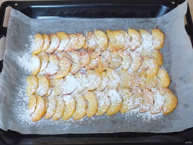 Возьмите противень. Застелите пергаментом и смажьте тонким слоем растительного масла. Выложите ломтики персиков. Сверху присыпьте их крахмалом (2 ст.л.). Включите духовку на 180 градусов.