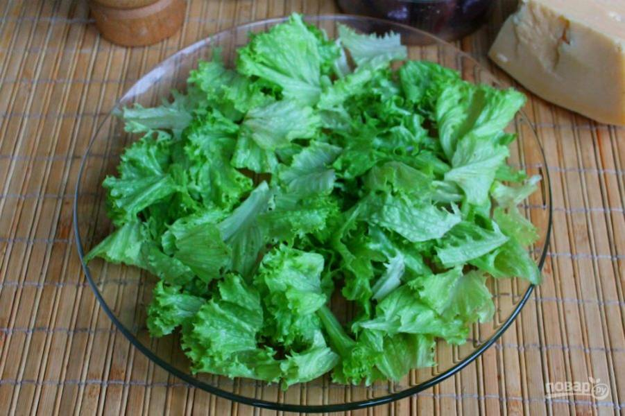Листья салата разделяем на кусочки и выкладываем на плоскую тарелку.