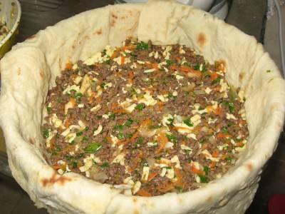 4. Примерно половину начинки выложите в форму. Тут можно экспериментировать и дополнять классический рецепт запеканки из лаваша с фаршем другими ингредиентами.