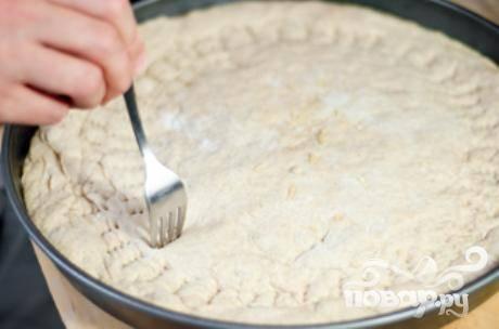 5. Готовое тесто ударить об стол и раскатать на посыпанной мукой поверхности в круг диаметром примерно 35 см. Выложить пиццу в форму. Разогреть духовку до 260 градусов. Сформировать декоративную корочку по краю пиццы. Накрыть крышкой и дать подняться, пока тесто не увеличится в объеме вдвое, около 30-40 минут. Несколько раз наколоть поверхность вилкой.