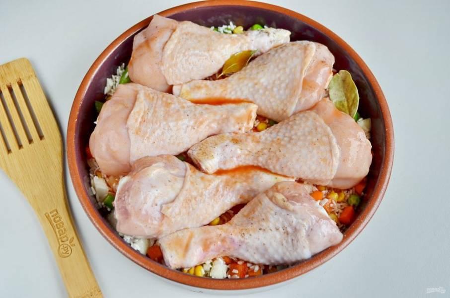 Томатную пасту разведите кипятком, добавьте соль по вкусу. Залейте этой смесью рис. Накройте форму фольгой и отправьте в духовку. Запекайте при 180 градусах до полной готовности мяса и риса. Время зависит от вашей духовки. Ножки будут готовы, когда от косточки отойдет мясо.