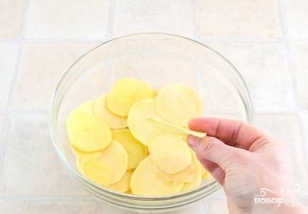 1. Перед тем, как приготовить домашние картофельные чипсы в духовке, помойте и очистите картофель. Затем нарежьте его слайсами приблизительно по 2 миллиметра толщиной. Промокните бумажным полотенцем от лишней влаги.