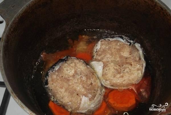 Репчатый лук очистите и нарежьте крупными кольцами. Морковь тоже очистите и нарежьте толстыми кольцами (около 2 сантиметров толщиной). В казане разогрейте растительное масло, выложите на дно лук и морковь. Из фарша сформируйте котлетки, оберните их кожей щуки. Положите котлетки в казан на овощи.