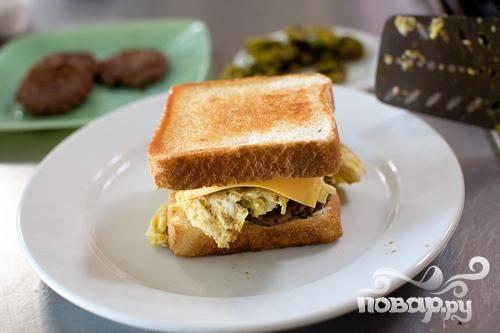 6. Готовые ломтики хлеба смазать майонезом или горчицей. Затем выложить колбасу, яйца, халапеньо и сыр. Накрыть сверху оставшимися ломтиками хлеба, разрезать по диагонали и подавать.