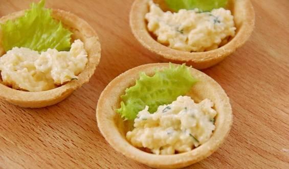4. Теперь начиняем тарталетки: сбоку выкладываем часть листа салата, а остальное пространство заполняем начинкой из сыра.