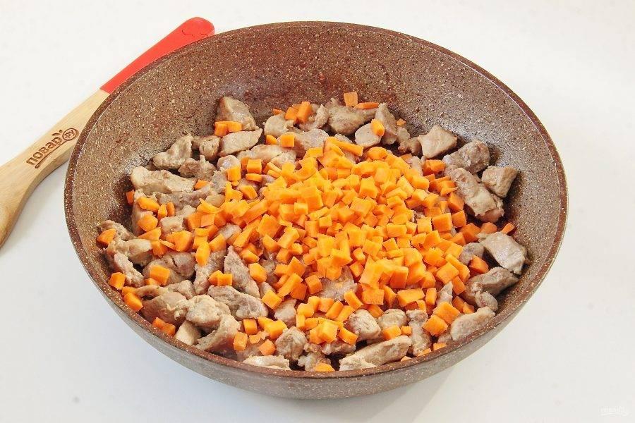 Затем огонь убавьте и по очереди добавьте овощи, каждую партию обжаривая примерно по 5 минут. Сначала морковь, нарезанную кубиками.