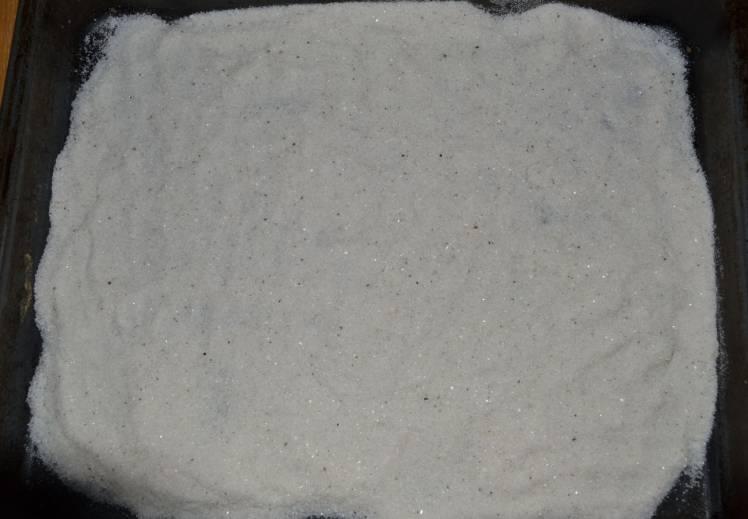 Достаем из духовки противень и высыпаем на него килограмм соли, равномерно ее распределяем.