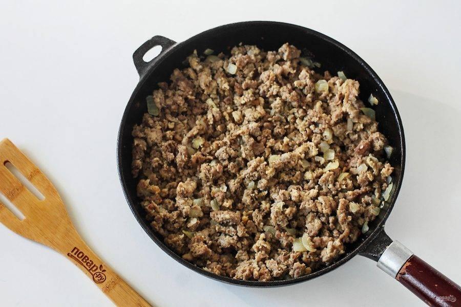 Переложите содержимое сковороды пока на тарелку, а на этой же сковороде обжарьте нарезанную кубиками вторую луковицу. Добавьте фарш, соль по вкусу и любимые специи, готовьте до полной готовности фарша, разбивая в процессе все комочки лопаткой.