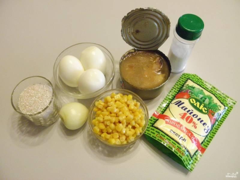 Подготовьте продукты для салата. Откройте консерву, слейте жидкость, оставьте буквально столовую ложку, чтобы салат был более сочным. Отварите яйца вкрутую, остудите их и очистите от скорлупы. Промойте и переберите рис, залейте стаканом воды и отварите до готовности, посолите по вкусу.