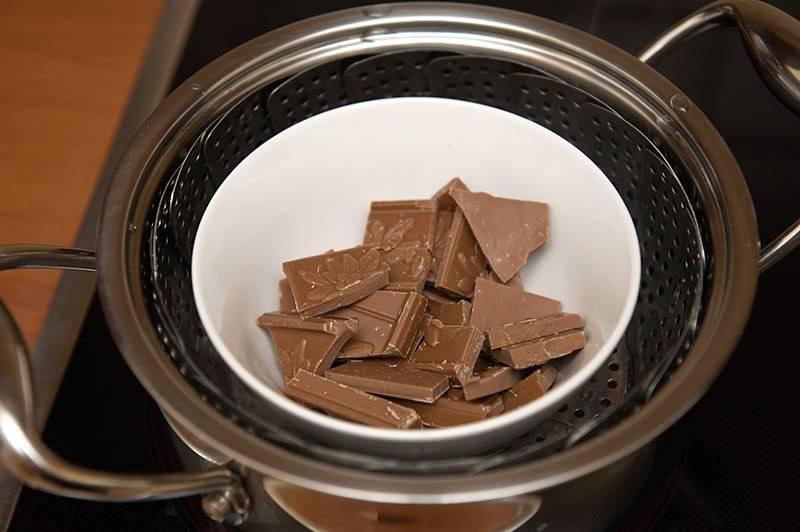4. Смешиваем обе смеси и продолжаем взбивать. Теперь заливаем полученную массу в форму для запекания и отправляем в разогретую до 200 градусов духовку на 20-25 минут. Огонь немного убавляем (до 180 градусов) и запекаем корж до готовности. Тем временем нужно растопить шоколад. Черный или молочный - по вашему вкусу, но для этого торта будет вкуснее молочный. Я обычно беру плитку готового молочного шоколада, разламываю его и растапливаю на водяной бане.