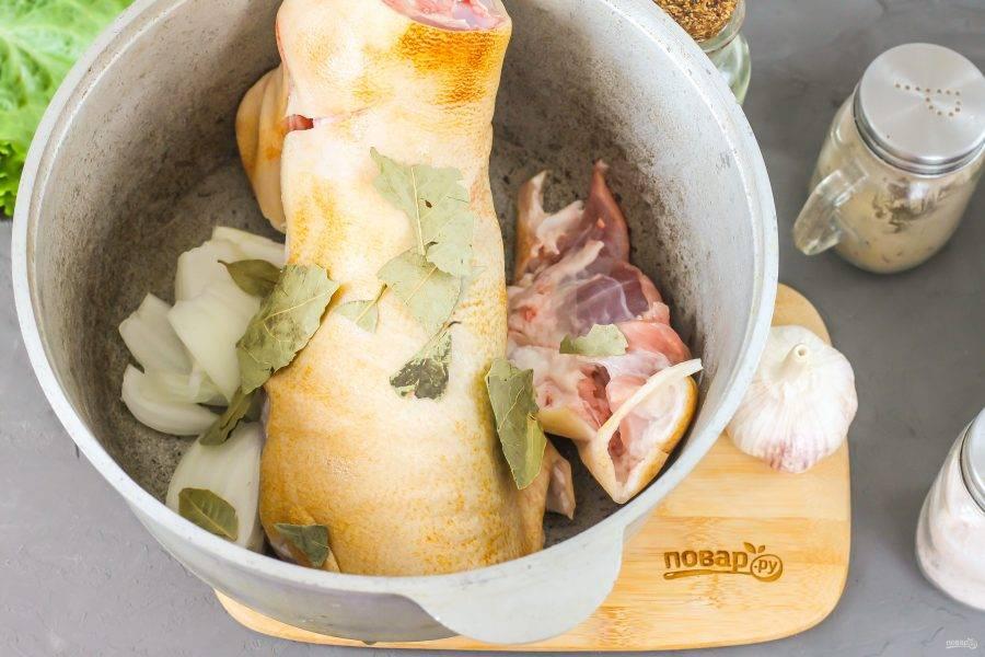 Выложите очищенную рульку в казан или в кастрюлю, всыпьте соль, лавровые листья. Очистите репчатый лук, промойте и разрежьте на четыре части. Добавьте в казан. Влейте теплую воду и отварите рульку в течение 2-3 часов, удалив образовавшуюся пену шумовкой.