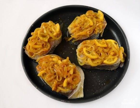 7. Жаропрочную форму смажьте маслом и выложите рыбку. Сверху аккуратно распределите лук с лимоном. Отправьте форму в разогретую до 190 градусов духовку минут на 10-12.