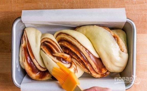 6. Смажьте тесто сливочным топленым маслом. Выпекайте булочки 30 минут в разогретой до 170-180 градусов духовке.
