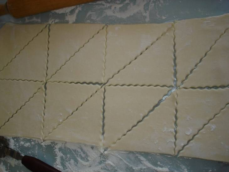 Для начала обжариваем грибы вместе с луком на растительном масле. Когда они остынут, добавляем к ним ложку сметаны и измельченную зелень, солим и перемешиваем. Теперь берем одну пластину теста и раскатываем ее в прямоугольник. Нарезаем прямоугольник на 8 квадратов, а каждый квадрат на 2 треугольника, то же самое делаем и со второй пластиной теста. Я для нарезки использую специальный фигурный нож, поэтому пирожки получаются очень красивые.