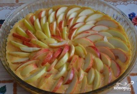 Смазываем форму для выпечки маслом, выкладываем в нее тесто, разравниваем. Затем раскладываем-вдавливаем дольки яблок в тесто. Посыпаем сахаром.