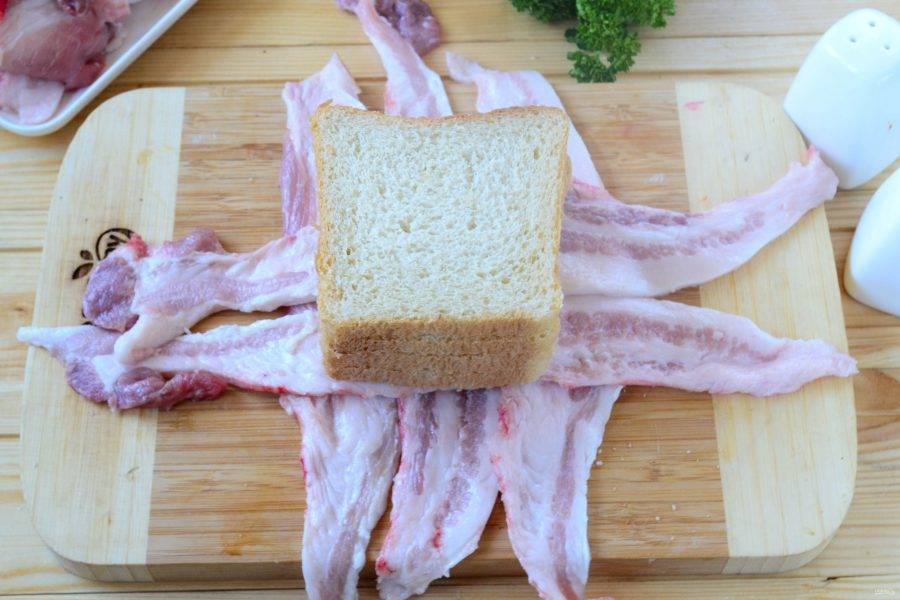 Крестом выложите ломтики бекона на рабочую поверхность. На середину положите сэндвич.
