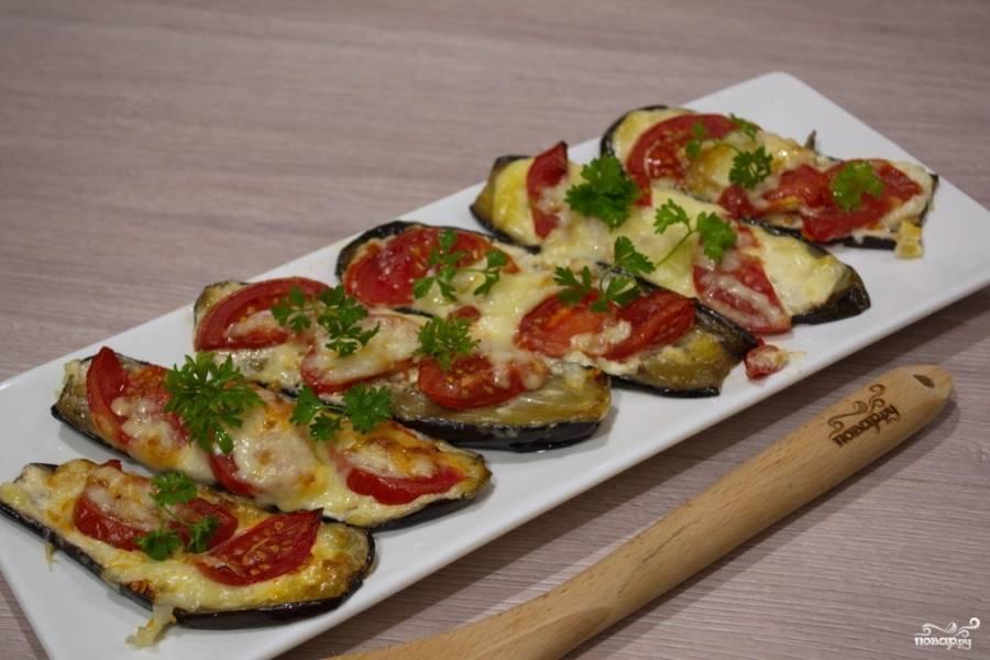 На баклажаны поверх майонеза выложите нарезанные полукольца помидоров, натрите на терке твердый сыр. Посыпьте сыром баклажаны.  Разогрейте хорошо духовку до температуры 180 градусов. Запекайте баклажаны в духовке 10-15 минут.
