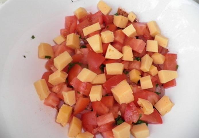 Сыр порежьте небольшими кубиками, добавьте в тарелку с мясом и помидорами. Посолите по вкусу и хорошо перемешайте.