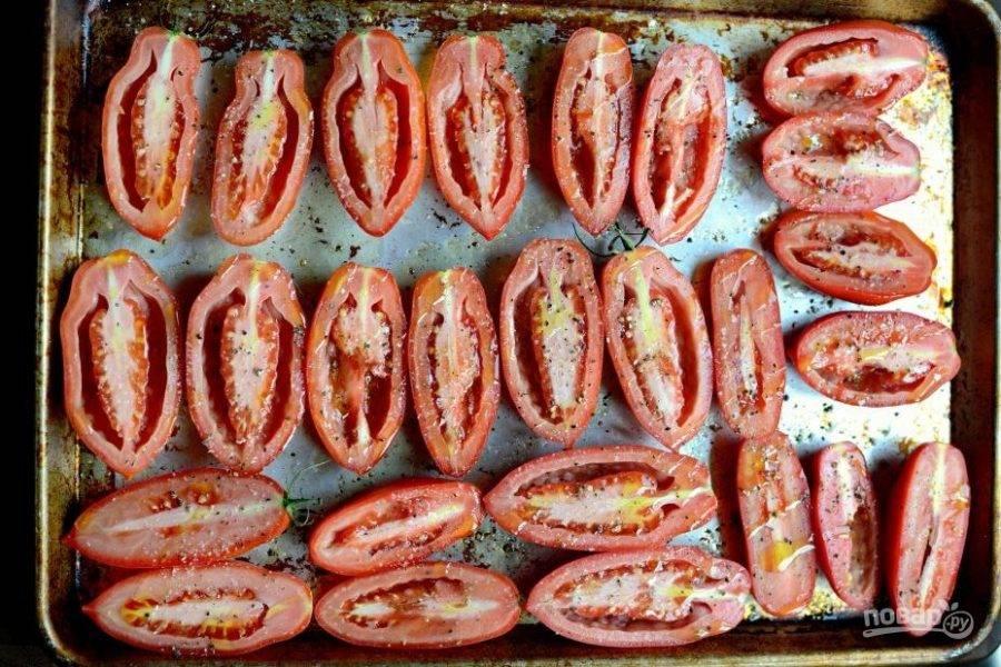 1. Помидоры разделите на половинки. Потом выложите на противень мякотью вверх. Посыпьте их перцем и солью, а также полейте маслом.