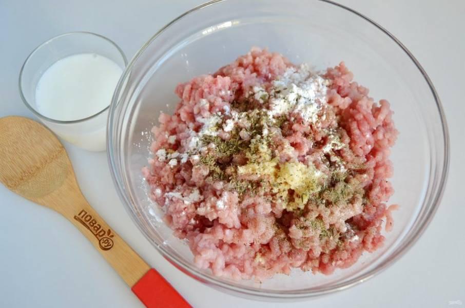 2. В фарш положите крахмал, чеснок, соль, перец, специи. Перемешайте. Влейте молоко и хорошенько вымешайте фарш.